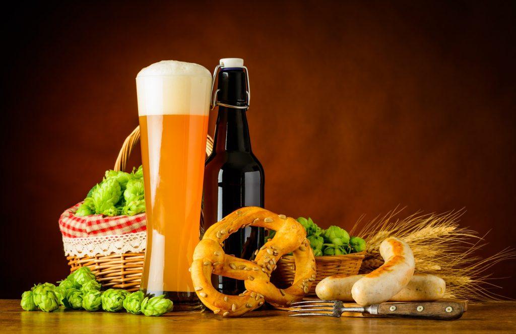 Vaso de cerveza de trigo alemana, acompañada de salchichas y pretzels